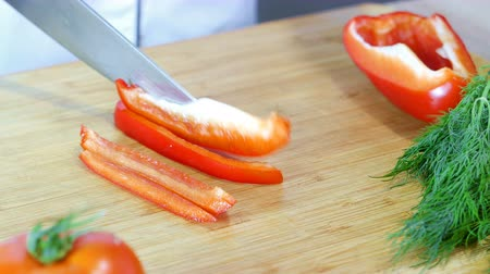 female cook cuts sweet pepper, hands closeup