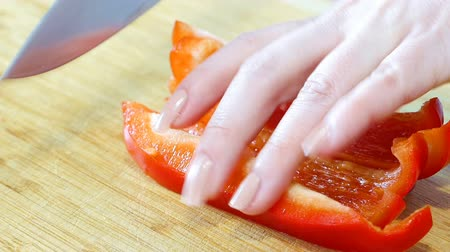 tagliere : female cook cuts sweet pepper, hands closeup