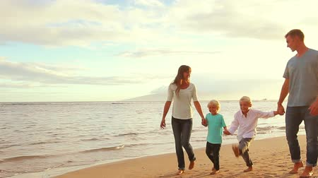 ailelerin : Happy Young Caucasian Family Walking on Sandy Beach at Sunset.