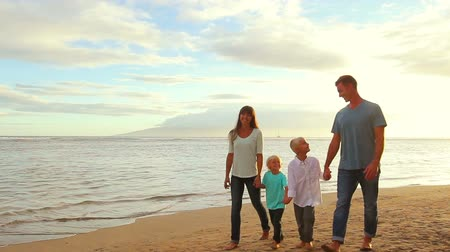 plaz : Happy Young Caucasian Family Walking on Sandy Beach at Sunset.