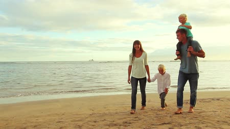plaz : Happy Young Caucasian Family Walking on Sandy Beach at Sunset. Father Gives Son a Piggy Back Ride.