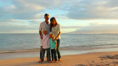 ailelerin : Happy Young Caucasian Family Posing on Sandy Beach at Sunset.