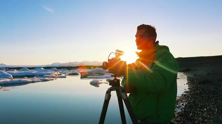 fényképész : A photographer takes photo of icebergs in Glacier Lagoon at Sunrise. Jokulsarlon estuary