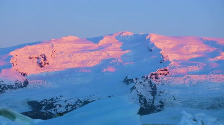 ledovec : Beautiful Pan of Pink Sunrise Light on Snowy Mountain Peaks. Jokulsarlon Dostupné videozáznamy
