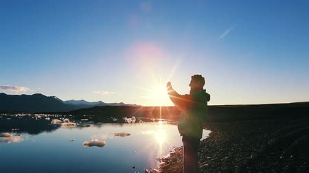 по телефону : Silhouette of Young Male Tourist Taking Pictures with Smart Phone at Sunrise on Adventure Vacation. Стоковые видеозаписи