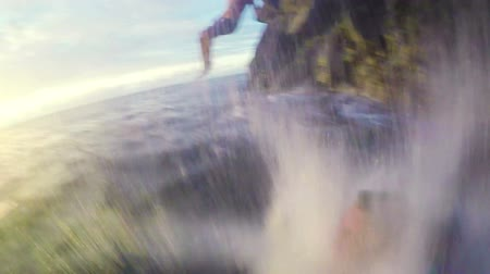 cliff : Two Young Men Jump off Cliff into Ocean at Sunset POV