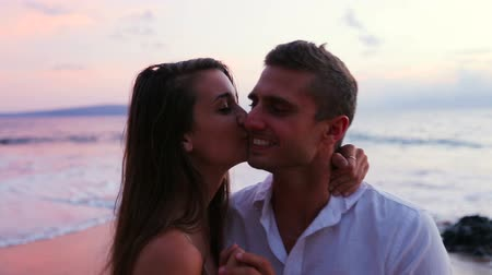 genç çift : Young Cute Brunette Couple Kissing and Posing for Camera on the Beach at Sunset