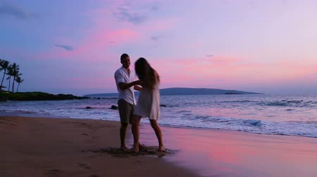 abraços : Romantic Young Couple Playing on the Beach in Hawaii at Sunset. Spinning and Holding Hands. Vídeos