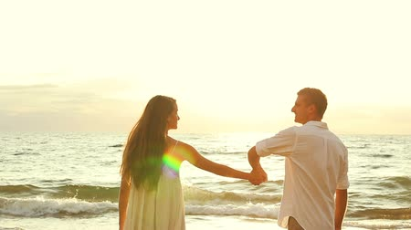 abraços : Romantic Couple Holding Hands and Kissing on the Beach at Sunset. The Man Spins the Woman Once and Walks Towards the Ocean.