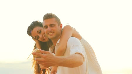 miłość : Young Happy Couple Taking Selfie Self Portrait and Kissing Outside At Beach