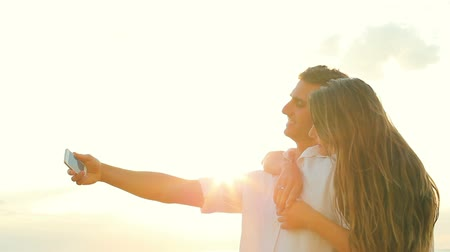 amantes : Young Happy Couple Taking Selfie Self Portrait and Kissing Outside At Beach