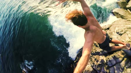 приморский : GOPRO POV of Athletic Young Man Jumping from Sea Cliffs into the Blue Ocean in Hawaii at Sunset.