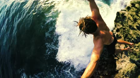 oceano : Athletic Young Man Jumping from Sea Cliffs into the Blue Ocean in Hawaii at Sunset.