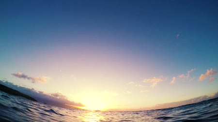 modrá obloha : Underwater Shot of Golden Sunset Rays of Light as the Camera Rises Above the Surface to show a Beautiful Sunset in Slow Motion. Dostupné videozáznamy