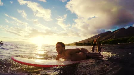 surf : Young Man Paddles a Surfboard Through Golden Sunset in the Blue Ocean in Hawaii in Slow Motion