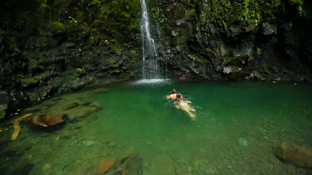 hayran olmak : Happy Attractive Young Brunette Couple Swimming Towards the Base of a Giant Tropical Waterfall in a Blue Pond in Hawaii Stok Video