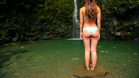 ülő : Beautiful Young Brunette Woman from the back Standing Under a Big Waterfall in Hawaii in a small light blue bikini Stock mozgókép