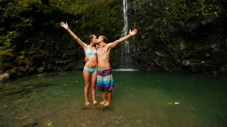 évad : Romantic Travel Honeymoon Concept. Happy Couple Kissing with Arms Raised Under a Waterfall in Hawaii. Attractive Model Brunettes. Stock mozgókép