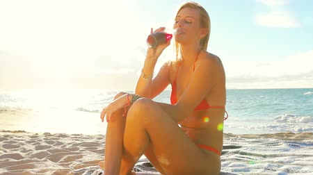 szörfös : Summer Fun Beach Lifestyle. Beautiful Attractive Young Blonde Woman Sitting on a Blanket Drinking a Cold Juice in a Glass Bottle. Lens Flares. Stock mozgókép