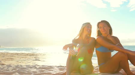 évad : Summer Fun Beach Lifestyle. Beautiful Attractive Young Women Sitting Together on the Beach living active healthy life. Lens Flares.