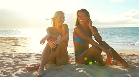 mulher jovem : Summer Fun Beach Lifestyle. Beautiful Attractive Young Women Sitting Together on the Beach living active healthy life. Lens Flares.