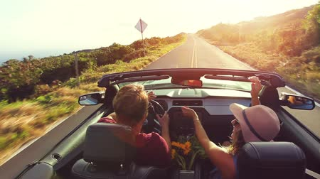descanso : Happy Young Hipster Couple Driving Convertible on Country Road into Sunset. Arms Raised. Romantic Freedom Vacation Concept. 20s-30s.