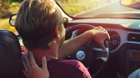 lifestyle : Happy Young Handsome Man Driving Convertible on Country Road. Close Up Steadicam Shot.