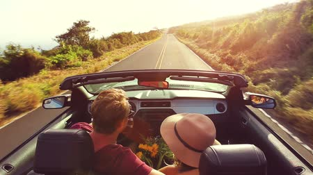 samochody : Happy Young Mixed Race Couple Driving Convertible on Country Road into Sunset. Romantic Freedom Vacation Concept. Man Has Arm Around Latina Woman