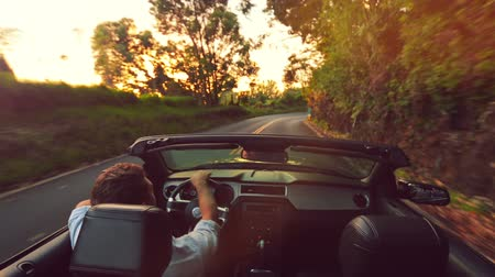 vie : Felice Giovane bello Driving Convertible su strada campestre a Sunrise. Steadicam Girato con il sole riflesso. Freedom Travel Concept Vacation.