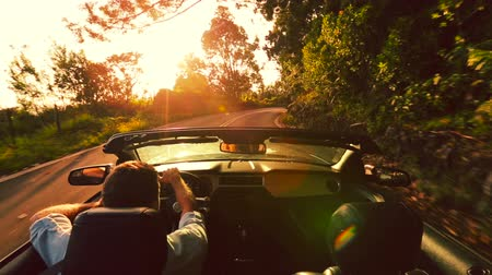 özgürlük : Happy Handsome Young Man Driving Convertible Car into Sunrise on Country Road. Steadicam Shot with Sun Flare. Freedom Travel Vacation Concept.