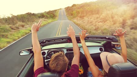 özgürlük : Happy Young Hipster Couple Driving Convertible on Country Road into Sunset. Arms Raised. Romantic Freedom Vacation Concept. 20s-30s.