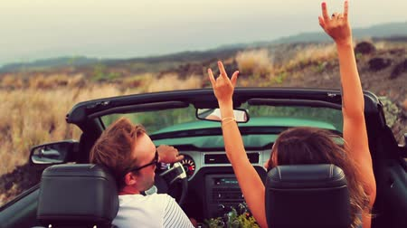 kabarık : Happy Young Attractive Couple Driving Convertible on Country Road. Arms Raised. Romantic Freedom Vacation Concept. 20s-30s.