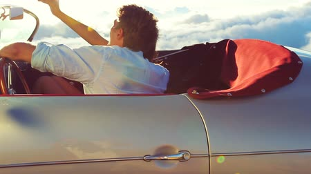 genç çift : Smartphone Selfie in a Classic Viontage Sports Car at Sunset. Happy Couple on Country Road in a Classic Vintage Sports Car. Steadicam Shot with Gorgeous Lens Flare. Romantic Freedom Love.