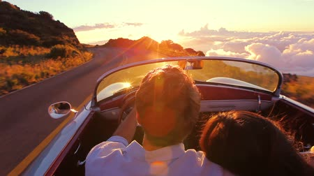 felicidade : Happy Couple Driving on Country Road into the Sunset in Classic Vintage Sports Car. Steadicam Shot with Flare. Romantic Freedom Love Concept. Stock Footage