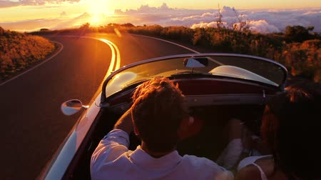 kabarık : Happy Couple Driving on Country Road into the Sunset in Classic Vintage Sports Car. Steadicam Shot with Flare. Romantic Freedom Love Concept. Stok Video
