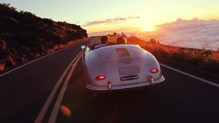 autó : Happy Couple Driving on Country Road into the Sunset in Classic Vintage Sports Car. Steadicam Shot with Flare. Romantic Freedom Love Concept. Stock mozgókép