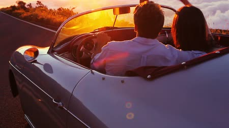 despreocupado : Happy Couple Driving on Country Road into the Sunset in Classic Vintage Sports Car. Steadicam Shot with Flare. Romantic Freedom Love Concept. Stock Footage