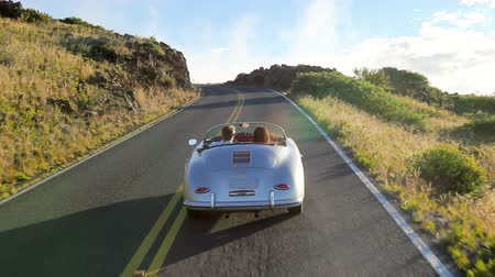droga : Happy Couple Driving Classic Convertible Car into Sunset on Country Road. Romantic Freedom Relaxing Road Trip Concept. Steadicam Shot.