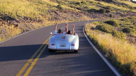 miłość : Happy Couple Driving Classic Convertible Car into Sunset on Country Road. Romantic Freedom Relaxing Road Trip Concept. Steadicam Shot.