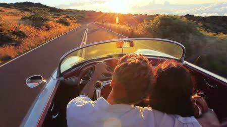 klassiek : Gelukkig Paar Rijden op de Landweg in de Zonsondergang in de Classic Vintage Car Cabriolet Sports. Steadicam Shot in Hawaii. Stockvideo