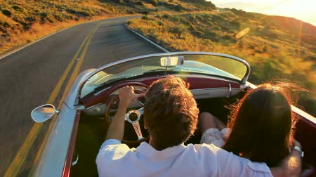 párosít : Happy Couple Driving on Country Road into the Sunset in Classic Vintage Sports Car. Steadicam Shot with Flare. Romantic Freedom Love Concept. Stock mozgókép