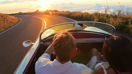 özgürlük : Happy Couple Driving on Country Road into the Sunset in Classic Vintage Sports Car. Steadicam Shot with Flare. Romantic Freedom Love Concept. Stok Video