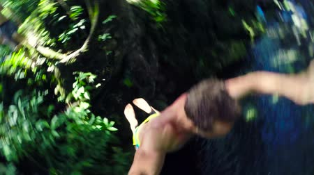 vodní sporty : POV Young Man Jumps off Cliff Into Water. Summer Extreme Sports Outdoor Lifestyle. Backlit Lush Green Jungle in Hawaii. Slow Motion