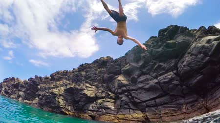 cliff : Young Man Flips Backflip off Cliff Into Ocean. Summer Fun Lifestyle.  Slow Motion