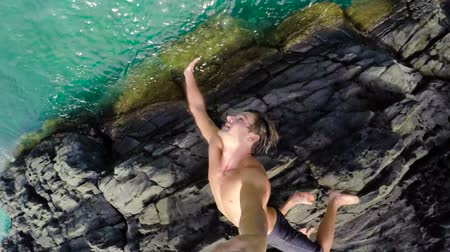 tourism : Extremely High Cliff Jump POV Young Man Backflips into Tropical Blue Ocean. Slow Motion.
