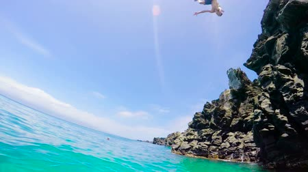 kayalık : Extremely High POV Back Flip Cliff Jump into Water in Slow Motion. Summer Adventure Fun Lifestyle. Stok Video