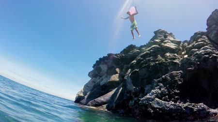 hareketli : POV of Athletic Young Man Jumping from Sea Cliffs into the Blue Ocean in Hawaii. Outdoor Active Lifestyle. SLOW MOTION