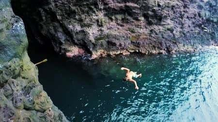 cliff : Extremely High Back Flip SLOW MOTION Cliff Jump into Water in front of a Sea Cave. Beautiful Sunny Day in Summer in Hawaii.