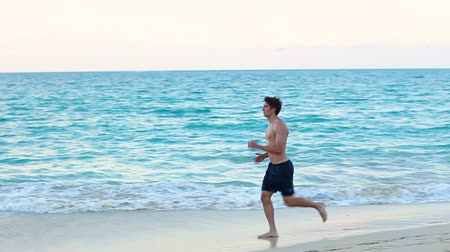 sprintel : Running sport man jogging on beach in full body length training outdoors for marathon run as part of active healthy lifestyle outside. Fit male fitness model exercising.