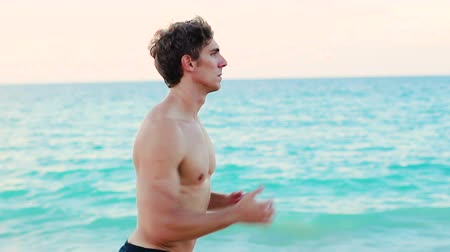 kimerül : Running sport man jogging on beach waist up shot training outdoors for marathon run as part of active healthy lifestyle outside. Fit male fitness model exercising. Stock mozgókép